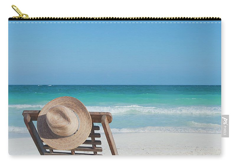 Scenics Carry-all Pouch featuring the photograph Beach Chair With A Hat On An Empty Beach by Sasha Weleber
