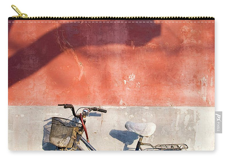 Chinese Culture Carry-all Pouch featuring the photograph Bicycle Against Red Wall by Frankvandenbergh