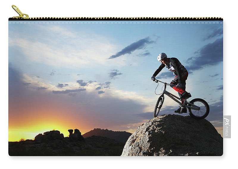 Sports Helmet Carry-all Pouch featuring the photograph Bike Rider Balancing On Rock Boulder by Thomas Northcut