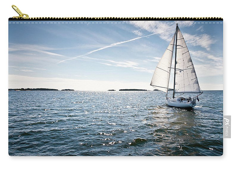 Recreational Pursuit Carry-all Pouch featuring the photograph Classic Yacht Sailing Away Against Blue by Jaap-willem