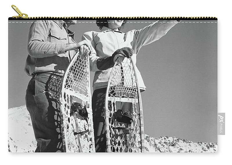Heterosexual Couple Carry-all Pouch featuring the photograph Couple Holding Snowshoes, Woman Pointing by Stockbyte