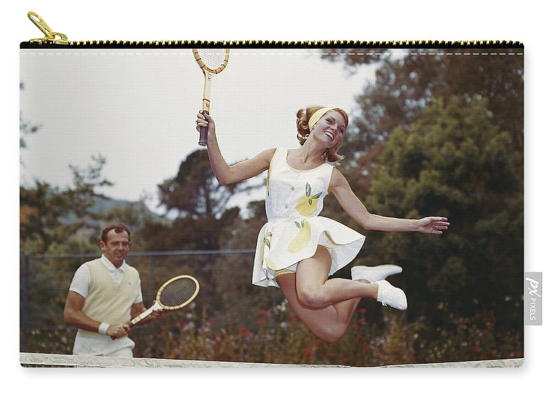 Heterosexual Couple Carry-all Pouch featuring the photograph Couple On Tennis Court, Woman Jumping by Tom Kelley Archive
