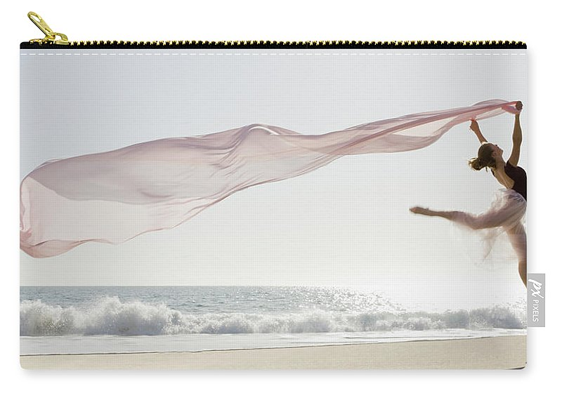 Ballet Dancer Carry-all Pouch featuring the photograph Dancer Leaping On Beach by Tetra Images - Pt Images