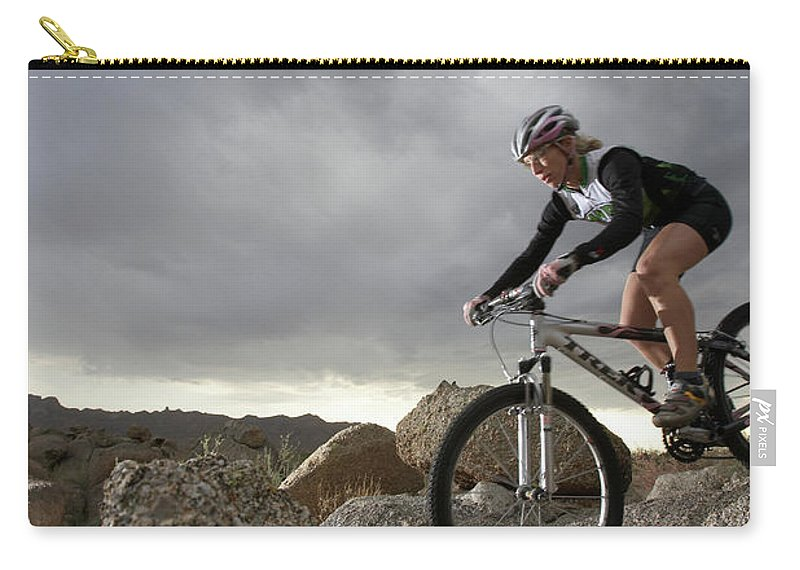 Sports Helmet Carry-all Pouch featuring the photograph Female Rider Mountain Biking Between by Thomas Northcut