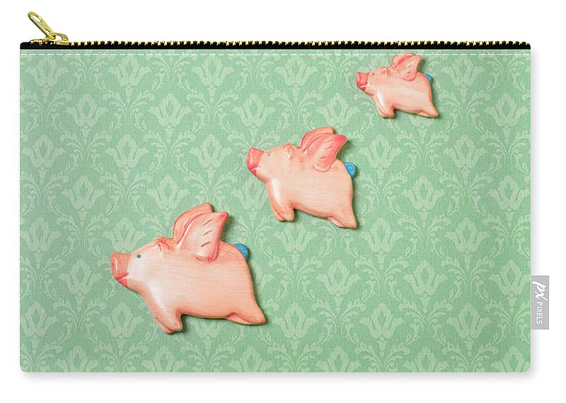 Disbelief Carry-all Pouch featuring the photograph Flying Pig Ornaments On Wallpapered by Peter Dazeley