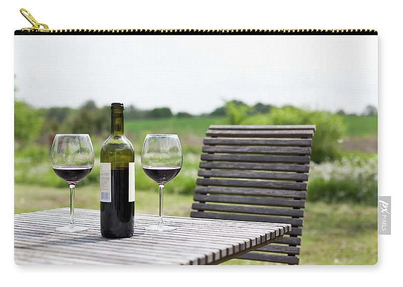 Five Objects Carry-all Pouch featuring the photograph Glasses And A Bottle Of Red Wine On An by Halfdark