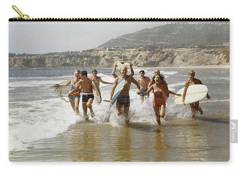 Young Men Carry-all Pouch featuring the photograph Group Of Surfers Running In Water With by Tom Kelley Archive