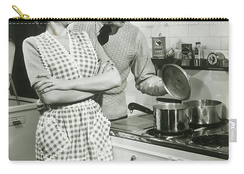 Heterosexual Couple Carry-all Pouch featuring the photograph Man Looking Into Pot In Domestic by George Marks