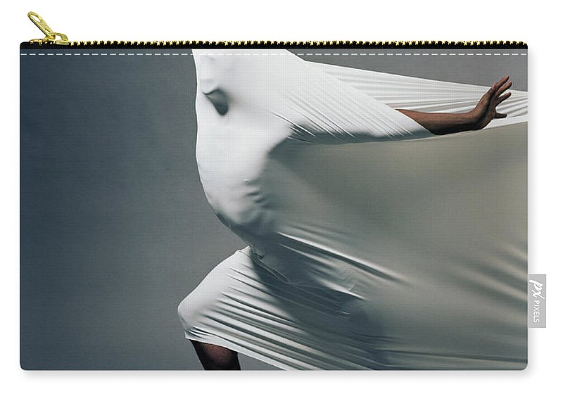 Hand Raised Carry-all Pouch featuring the photograph Man Pressing Into Fabric, Arms Extended by Pm Images