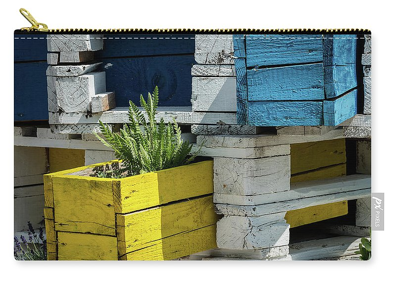 Gardening Carry-all Pouch featuring the photograph Old Pallet Painted White, Blue And Yellow Used As Flower Pot by Stefan Rotter