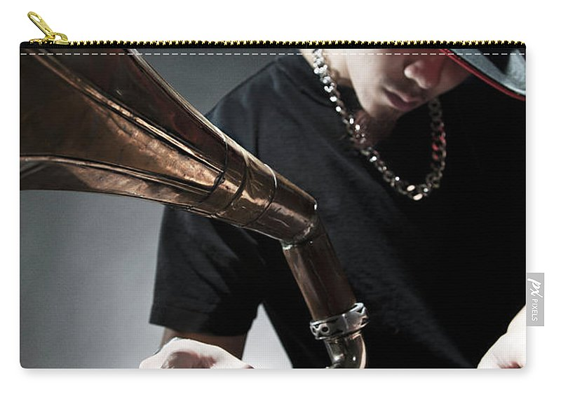Youth Culture Carry-all Pouch featuring the photograph Oriental Dj Using Old Gramophone To Mix by Justin Lambert