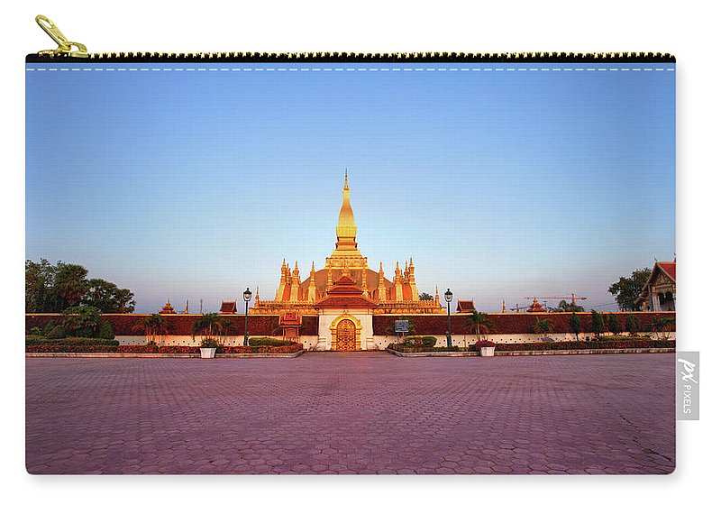 Monument Carry-all Pouch featuring the photograph Pha That Luang Stupa At Sunset by Fototrav
