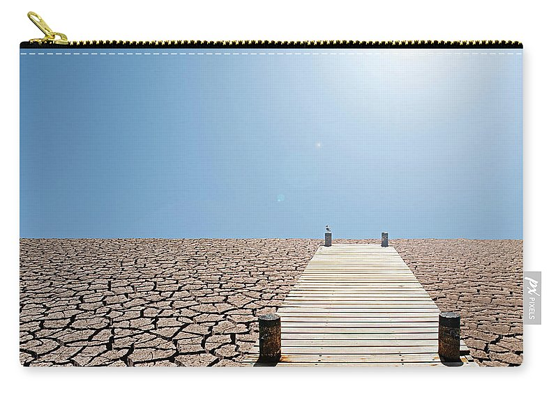 Environmental Damage Carry-all Pouch featuring the photograph Pier Over A Dry Lake Bed by John Lund