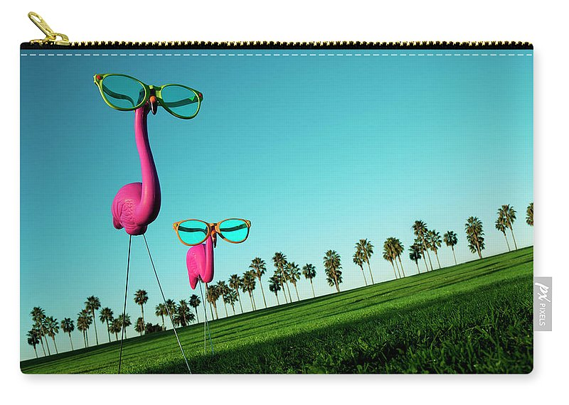 Artificial Carry-all Pouch featuring the photograph Plastic Pink Flamingos On A Green Lawn by Skodonnell