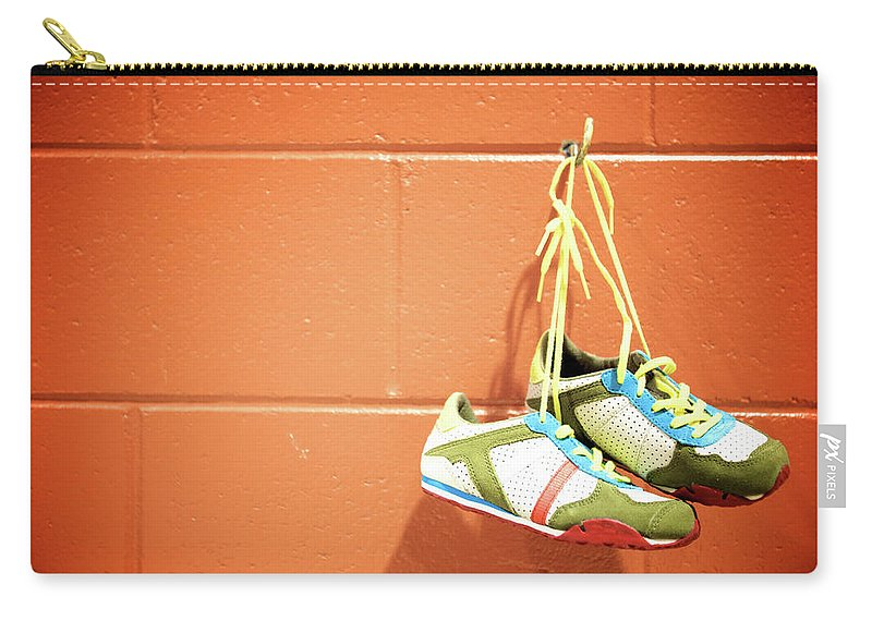 Hanging Carry-all Pouch featuring the photograph Runnig Shoes Hanging On A Hook by Pascalgenest