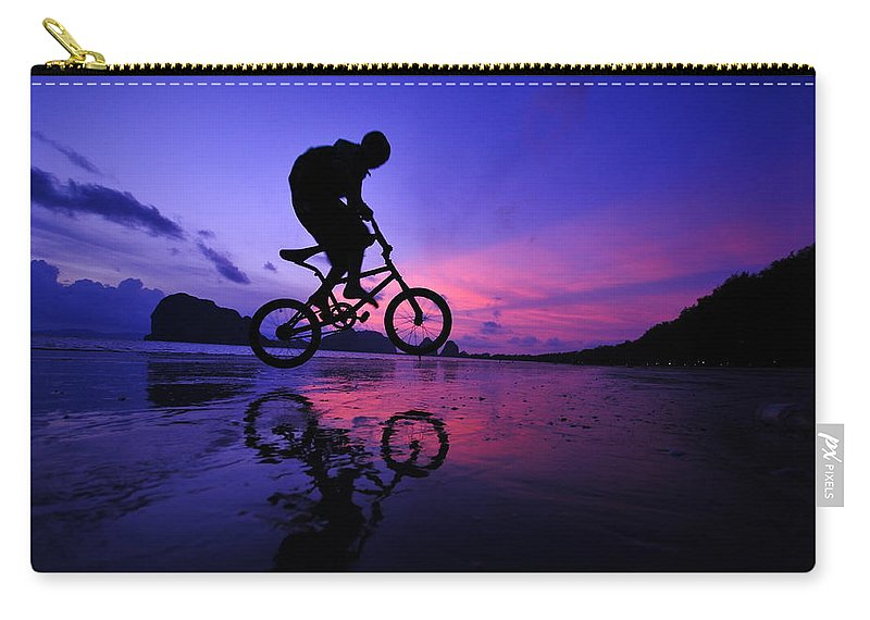 The Twilight Series Carry-all Pouch featuring the photograph Silhouette Of A Mountain Biker On Beach by Primeimages