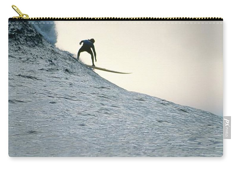 Scenics Carry-all Pouch featuring the photograph Silhouette Of A Surfer Riding A Wave by Dominic Barnardt