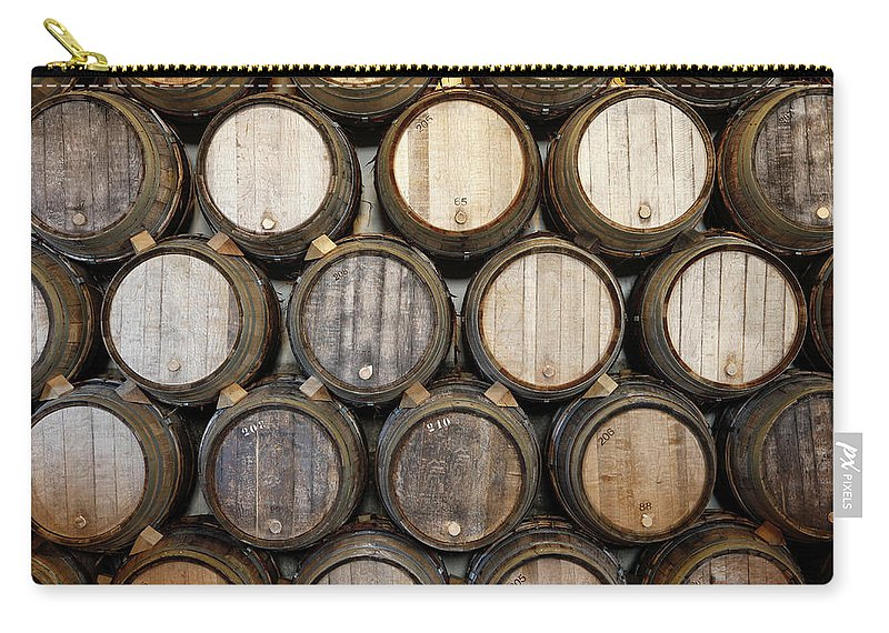 Alcohol Carry-all Pouch featuring the photograph Stacked Oak Barrels In A Winery by Marc Volk