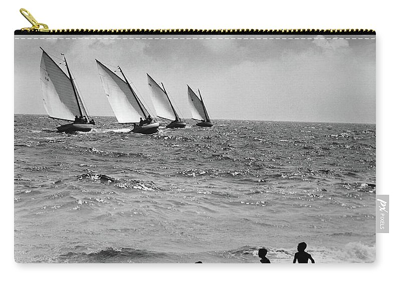 Following Carry-all Pouch featuring the photograph Three Boys Running Along Beach by Stockbyte