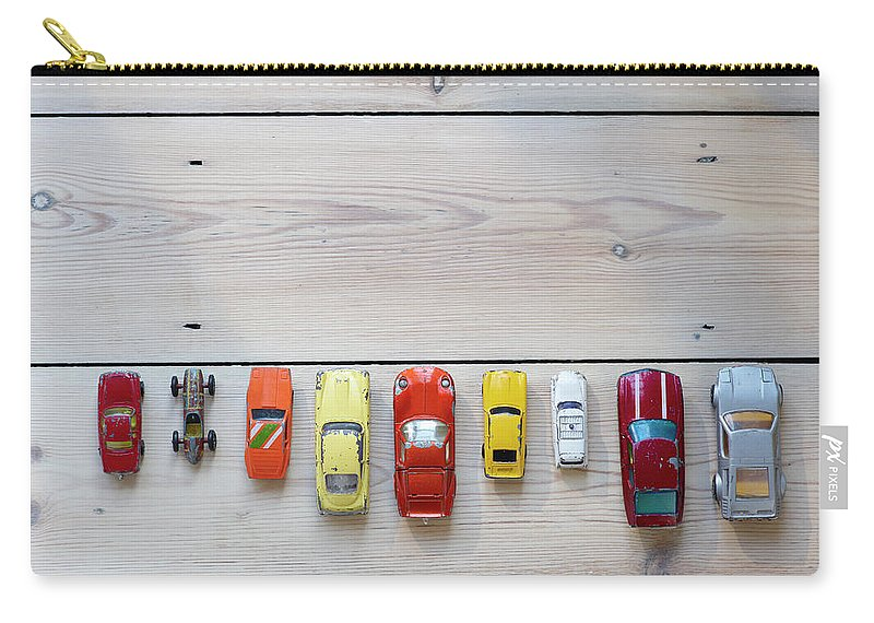 In A Row Carry-all Pouch featuring the photograph Toy Cars Lined Up In A Row On Floor by Dougal Waters