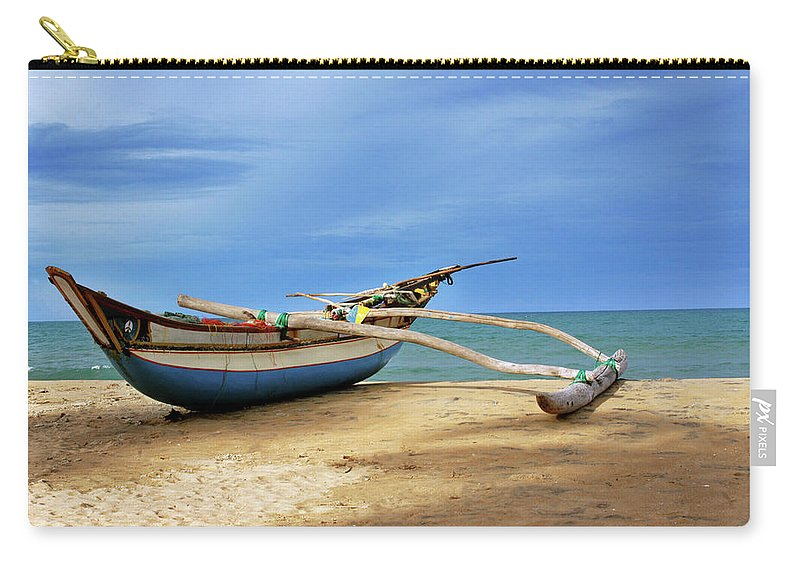 Tranquility Carry-all Pouch featuring the photograph Wooden Catamaran By The Sea Shore by Juavenita Alphonsus
