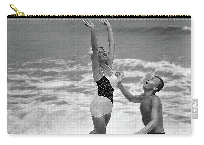 Young Men Carry-all Pouch featuring the photograph Young Couple Playing With Beach Ball At by Stockbyte