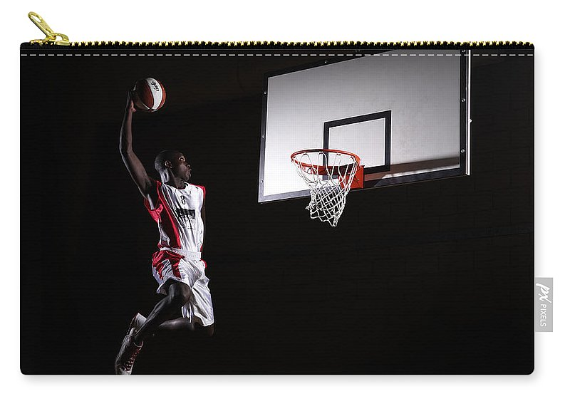 Human Arm Carry-all Pouch featuring the photograph Young Man In The Air About To Dunk The by Compassionate Eye Foundation/steve Coleman/ojo Images Ltd