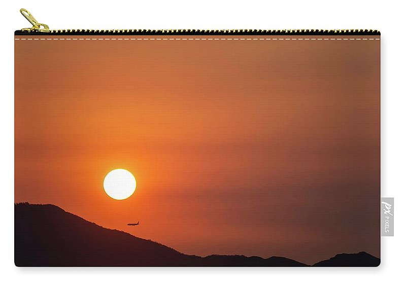 Sunset Carry-all Pouch featuring the photograph Red sunset and plane in flight by Hannes Roeckel