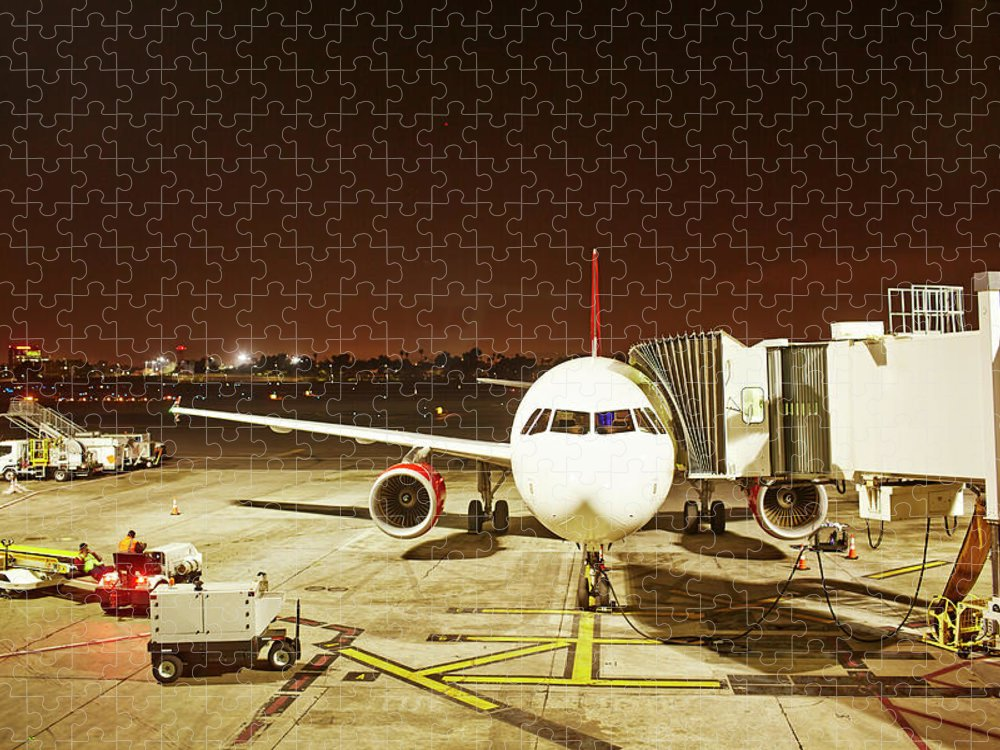 Passenger Boarding Bridge Puzzle featuring the photograph Airplane Parked At Jetway by Ballyscanlon