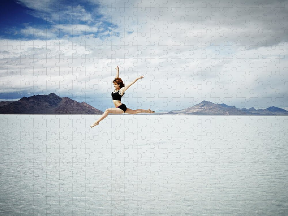 Ballet Dancer Puzzle featuring the photograph Ballerina Leaping In Mid-air Over Lake by Thomas Barwick