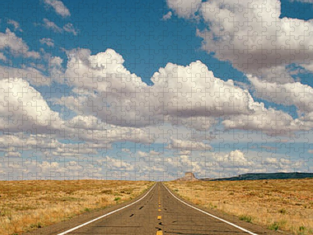 Scenics Puzzle featuring the photograph Desert Road With Cloud Formations Above by Gary Yeowell