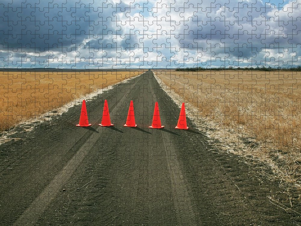 Orange Color Puzzle featuring the photograph Safety Cones Lined Up Across A Rural by Benjamin Rondel / Design Pics