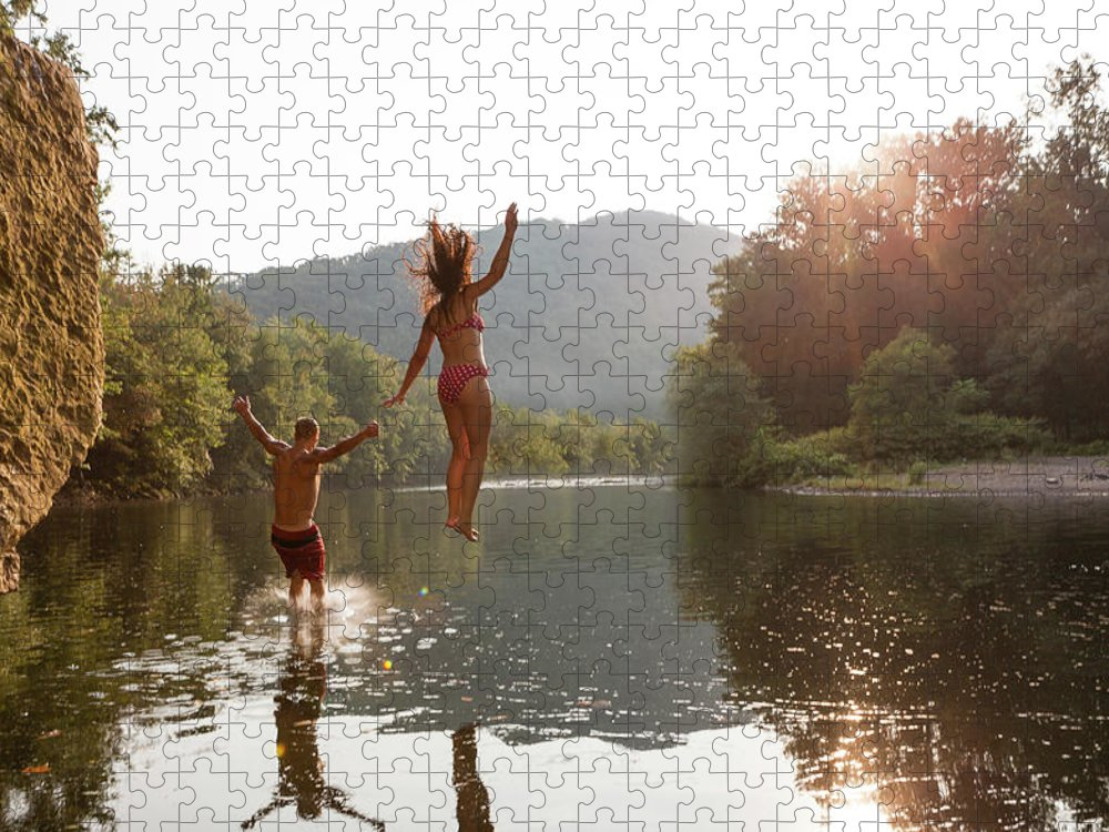 Young Men Puzzle featuring the photograph Young Couple Jumping Into River by Zave Smith