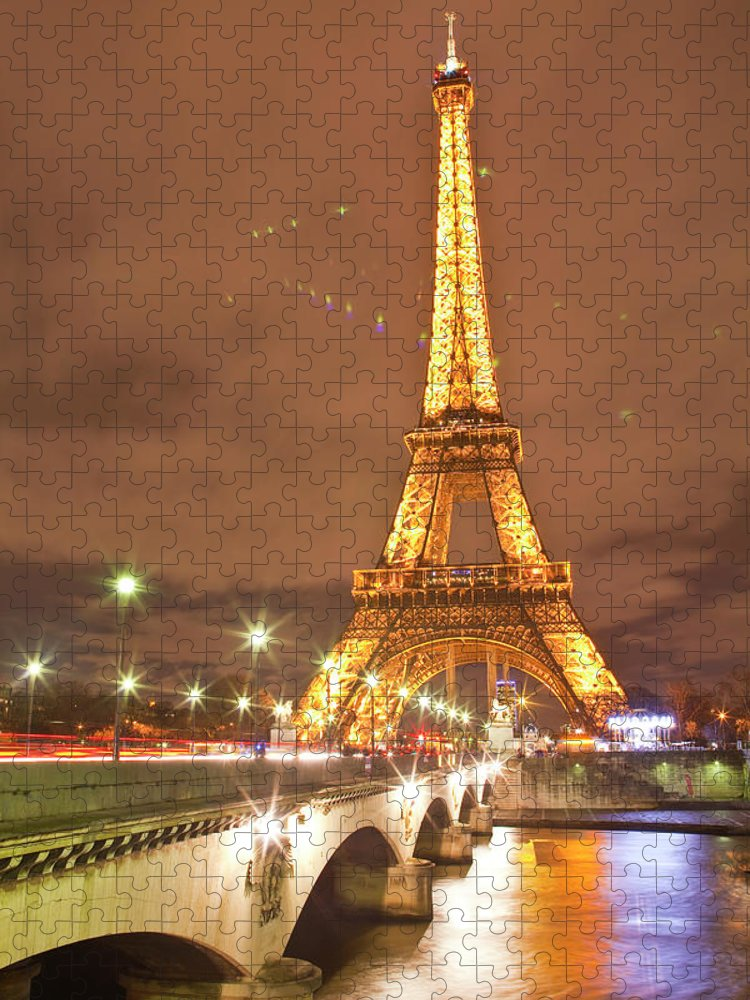 In A Row Puzzle featuring the photograph The Eiffel Tower Lit Up At Night In by Julian Elliott Photography
