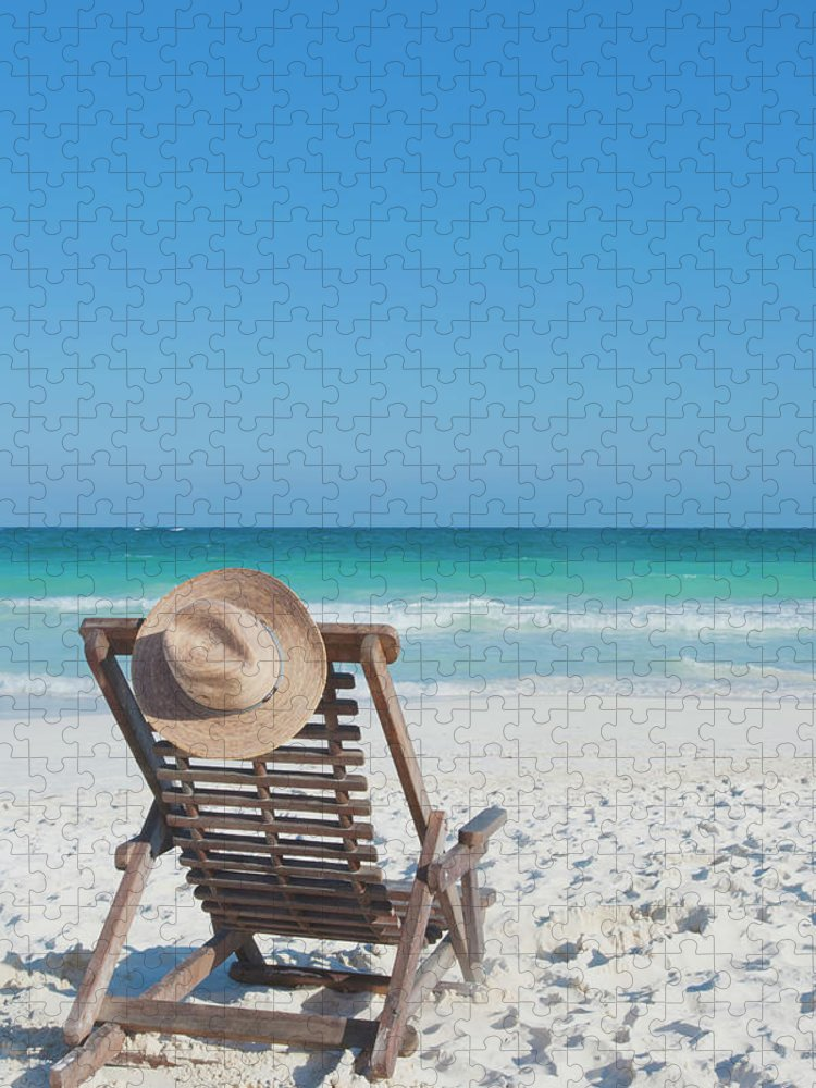 Scenics Puzzle featuring the photograph Beach Chair With A Hat On An Empty Beach by Sasha Weleber