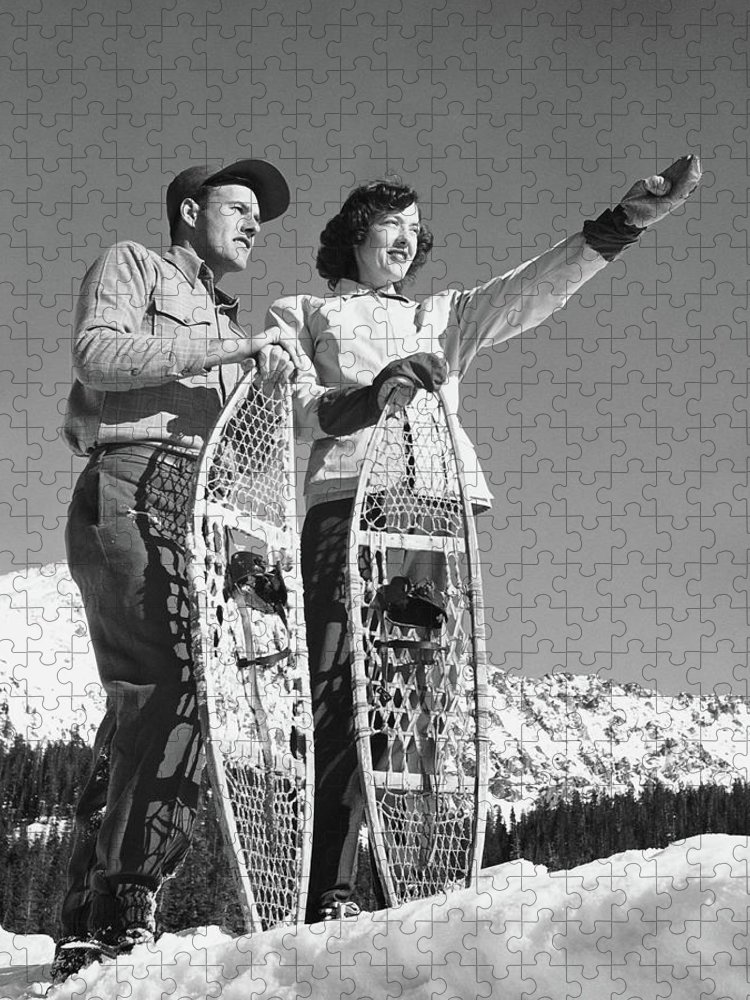 Heterosexual Couple Puzzle featuring the photograph Couple Holding Snowshoes, Woman Pointing by Stockbyte