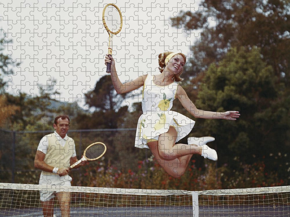 Heterosexual Couple Puzzle featuring the photograph Couple On Tennis Court, Woman Jumping by Tom Kelley Archive