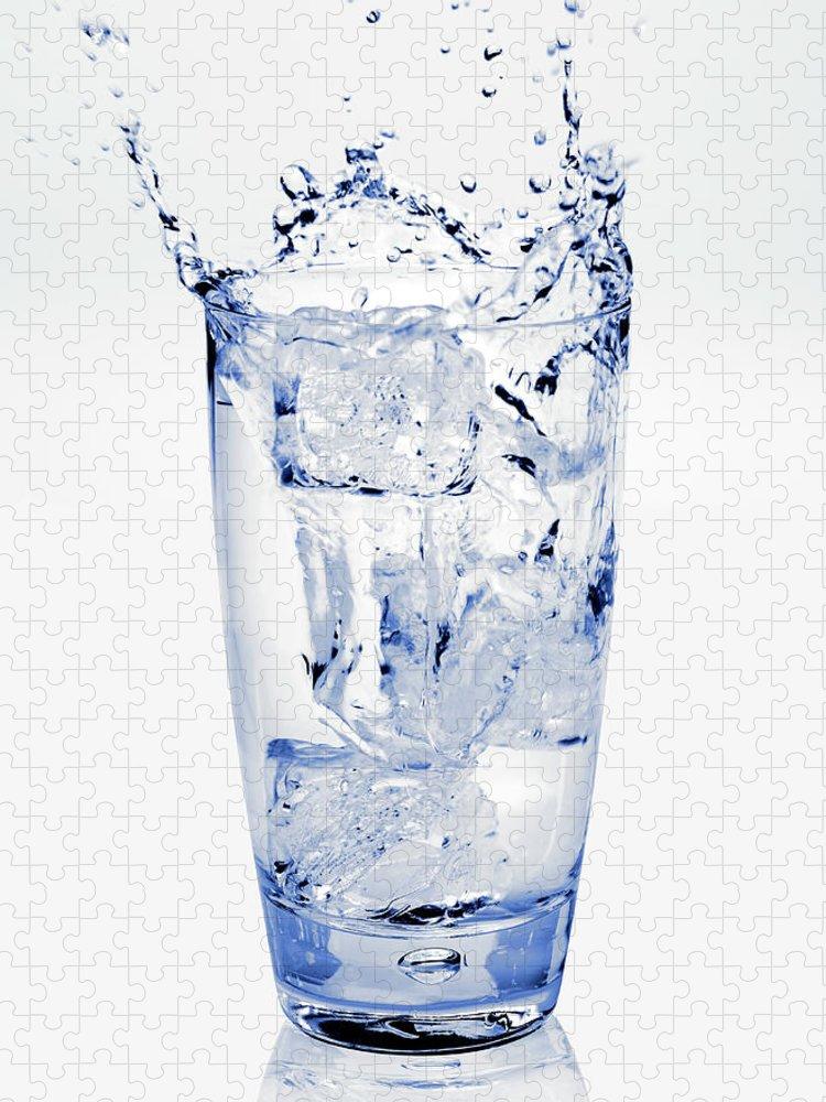White Background Puzzle featuring the photograph Glass Of Water Splashing Around by Maria Toutoudaki