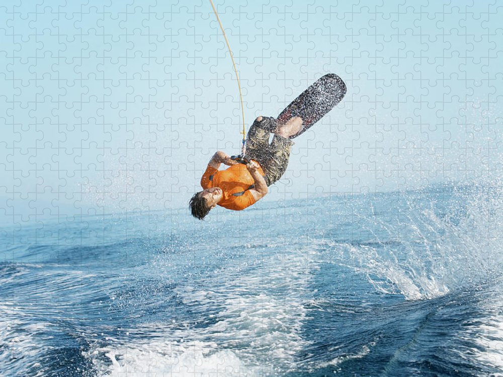 One Man Only Puzzle featuring the photograph Man Performing Wakeboarding Stunt At Sea by Paul Bradbury