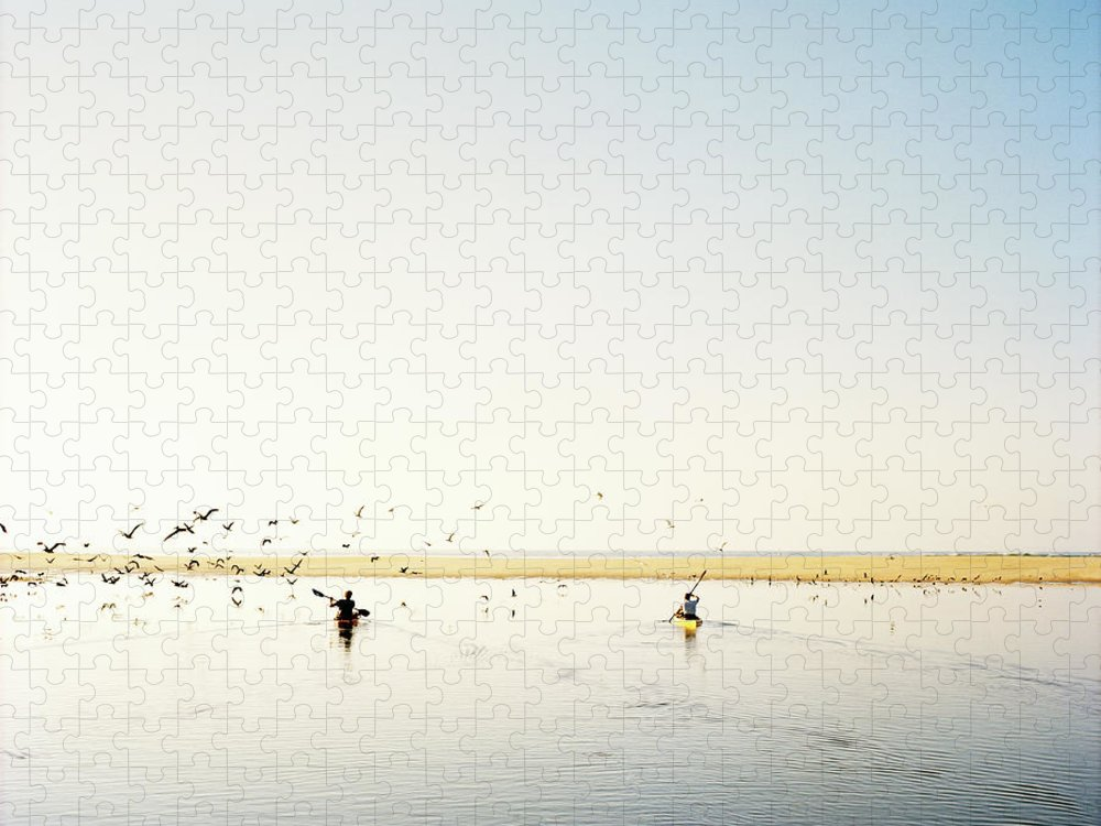 People Puzzle featuring the photograph Men Paddling Kayaks To The Beach by Julien Capmeil