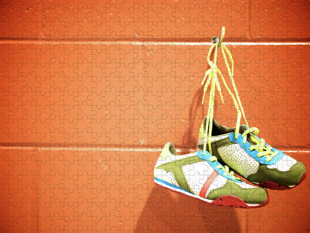 Hanging Puzzle featuring the photograph Runnig Shoes Hanging On A Hook by Pascalgenest