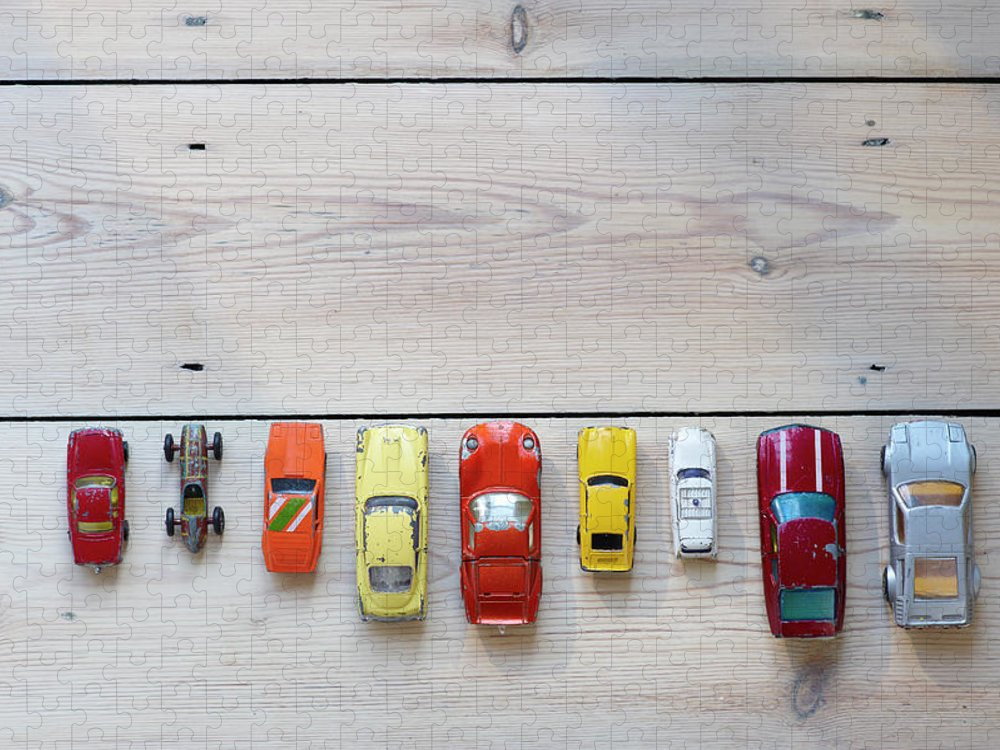 In A Row Puzzle featuring the photograph Toy Cars Lined Up In A Row On Floor by Dougal Waters
