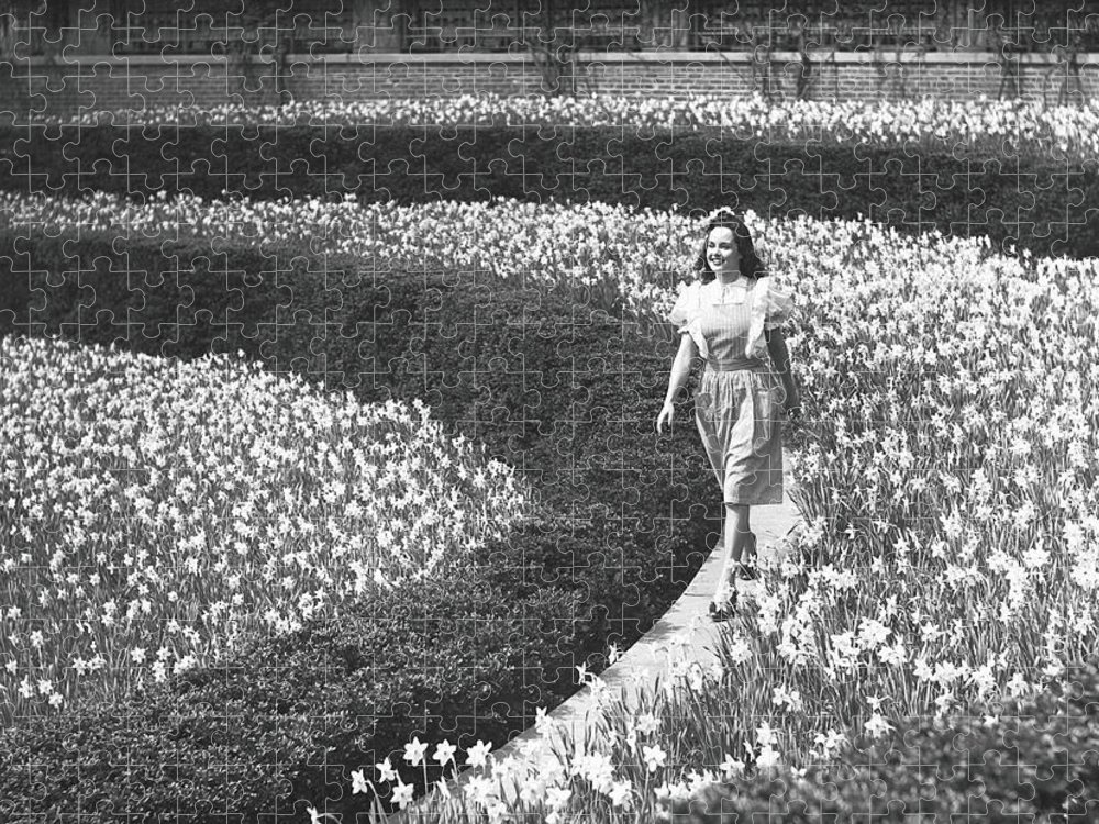Flowerbed Puzzle featuring the photograph Woman Walking On Flowerbed, B&w by George Marks