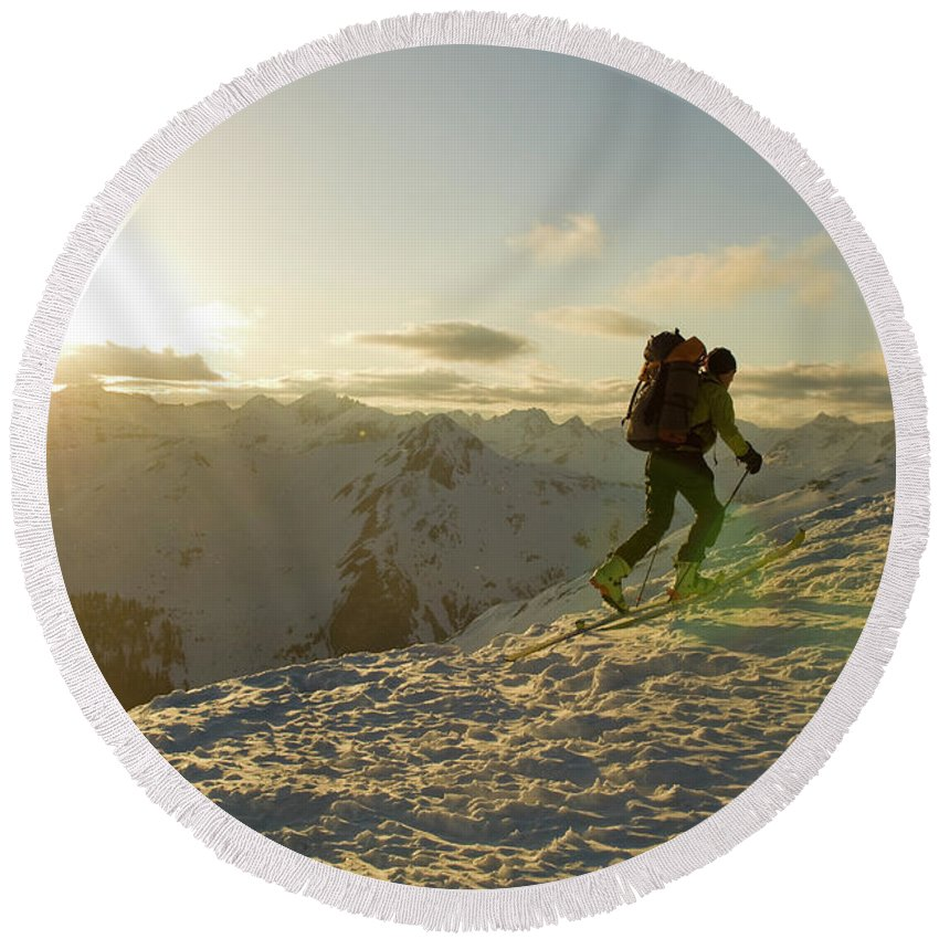 Adult Round Beach Towel featuring the photograph A Man Backcountry Skiing At Sunset by Kennan Harvey