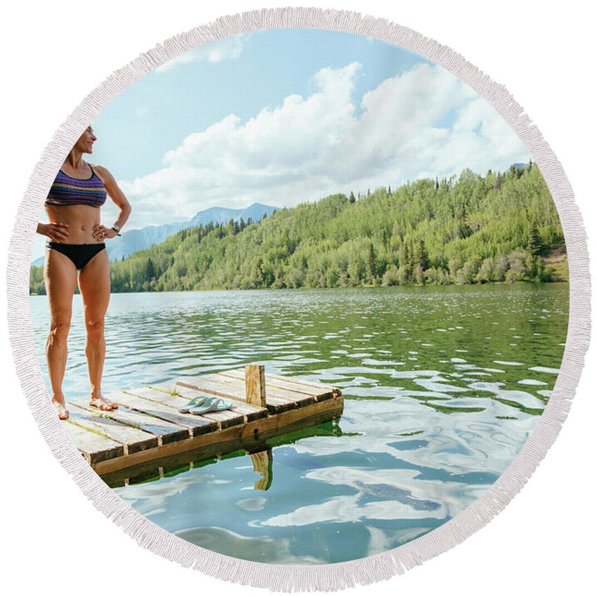 Alaska Round Beach Towel featuring the photograph A Woman Is Standing On A Jetty by Andrew Peacock