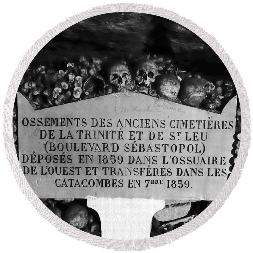 Paris Round Beach Towel featuring the photograph A Marker With Skulls And Bones In The Catacombs Of Paris France by Richard Rosenshein