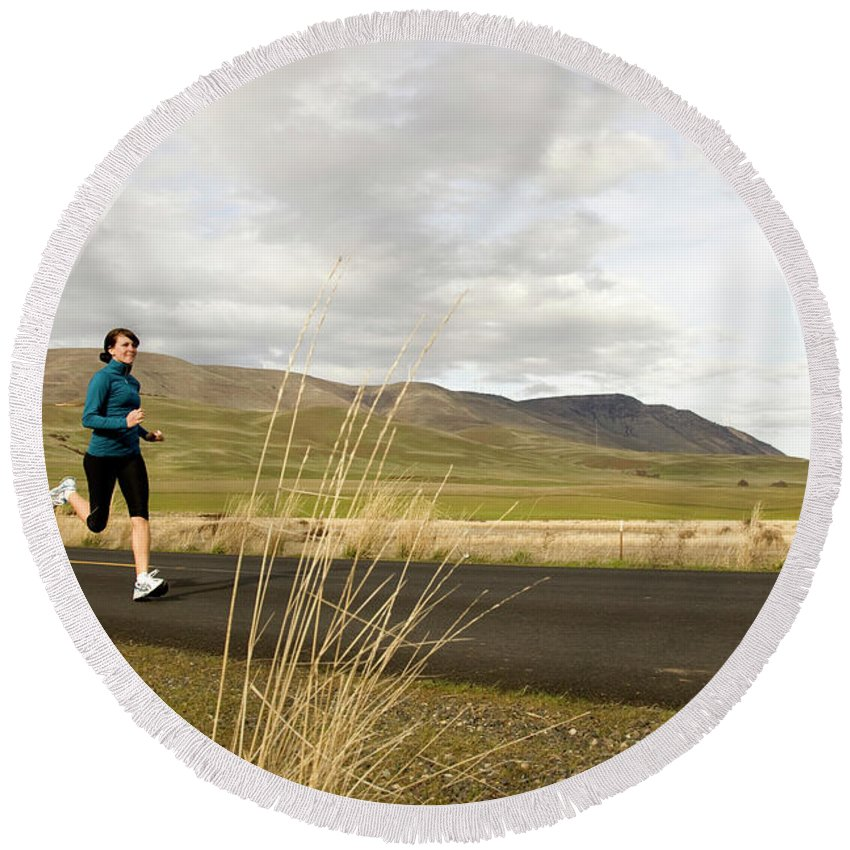 Adult Round Beach Towel featuring the photograph A Woman Out For A Jog In The Country by Jordan SIemens