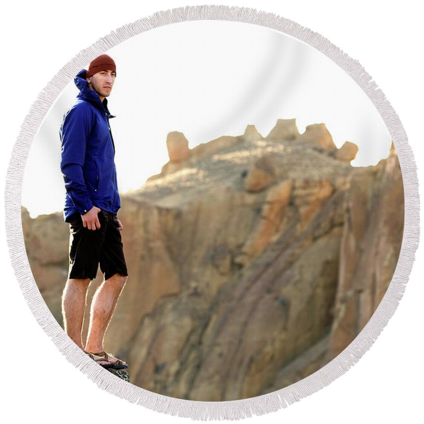 25-29 Years Round Beach Towel featuring the photograph A Man In A Blue Jacket Standing by Jordan Siemens