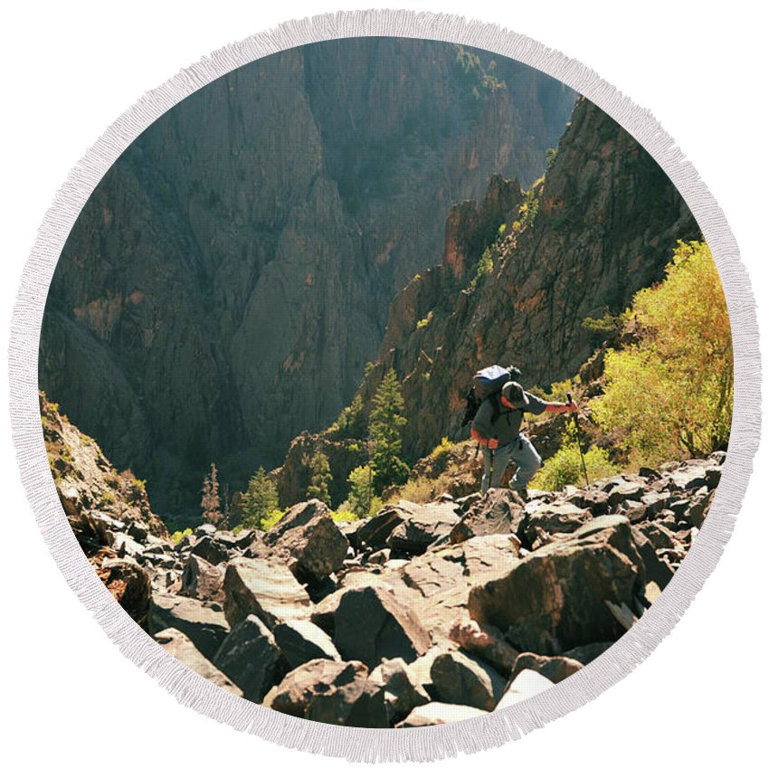 Backpack Round Beach Towel featuring the photograph A Man Navigates A Rock Scree Field by Bud Force