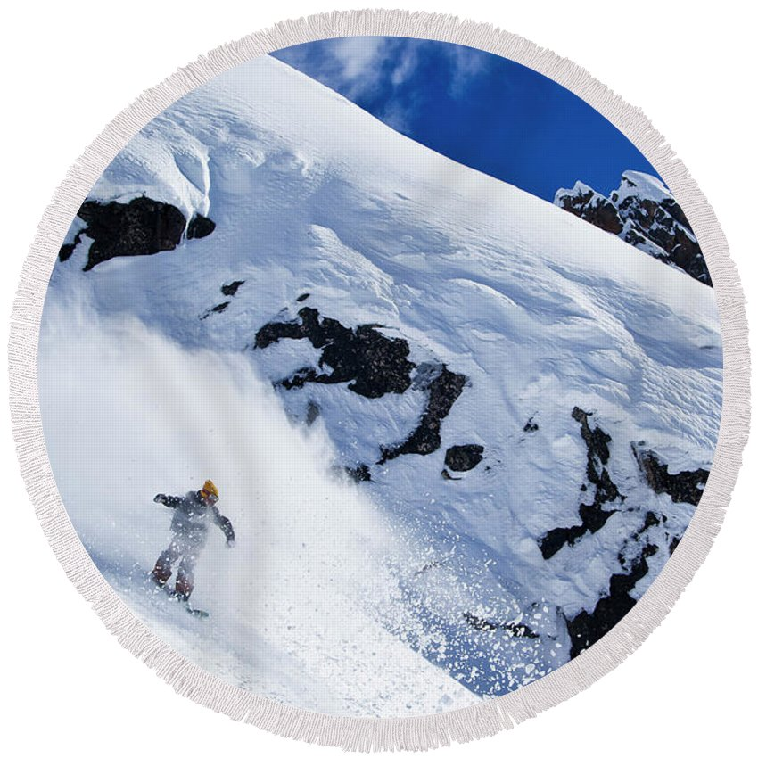 Outdoors Round Beach Towel featuring the photograph A Snowboarder Slashes Powder Snow by Ben Girardi